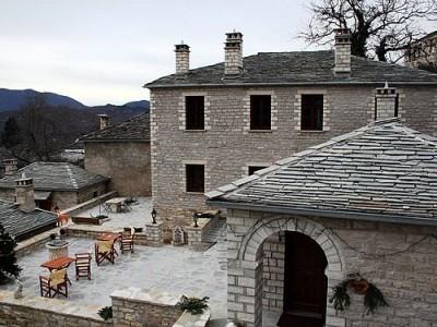 """""""Ο Ξενώνας του Νικόλα"""" αποτελείται από 5 δίκλινα, 5 τρίκλινα-τετράκλινα δωμάτια και 1 διαμέρισμα. Με πετρόχτιστα τζάκια ή χωρίς και παραδοσιακά έπιπλα, δίνουν την αυθεντική εικόνα μια Ζαγορίτικης κατοικίας. Άνετα, ρομαντικά, προσφέρουν ζέστη με αυτόνομη κεντρική θέρμανση. Στην κεντρική αίθουσα του ξενώνα (και αίθουσα πρωινού) θα διδαχθείτε πως είναι το αυθεντικό, πλούσιο Ζαγορίτικο πρωινό με φρέσκα αυγά του χωριού, αγνό μέλι, ντόπιο βούτυρο, μαρμελάδες και τις περίφημες αλευρόπιτες, ενώ τις υπόλοιπες ώρες της ημέρας μπορείτε να δοκιμάσετε αυθεντικούς ντόπιους μεζέδες και το παραδοσιακό μας τσίπουρο δίπλα απ' το τζάκι."""